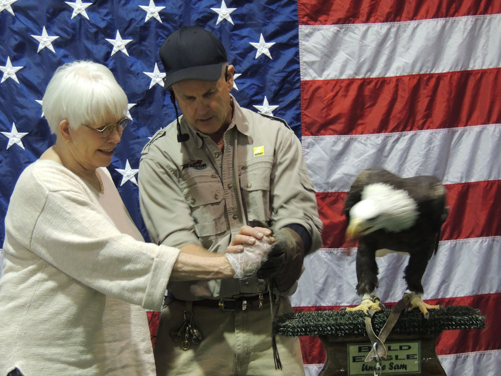 Fun with a friend - to the Raptor show at the Birding and Wild Life Festival Event - If you are volunteered you can feed the American Eagle - and we did volunteer - What a fun trooper she was - she fed the Eagle. He is moving to grab the food